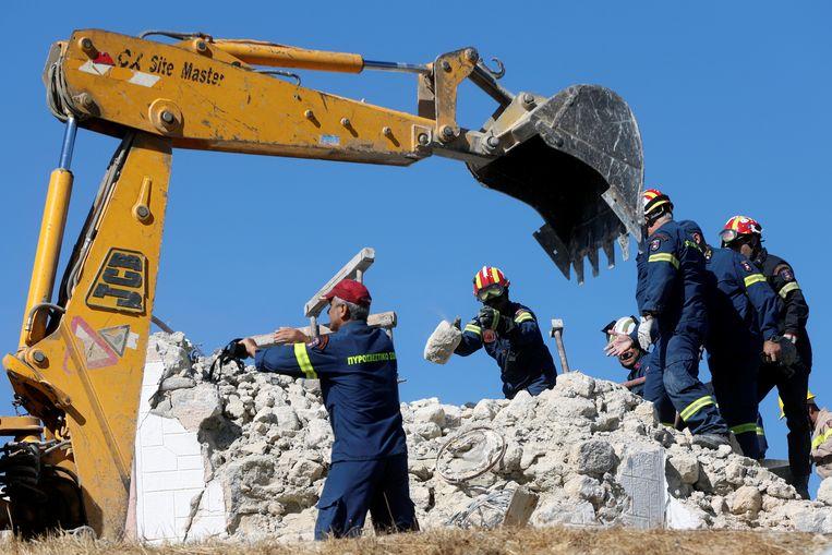 Brandweermensen zoeken naar slachtoffers onder het puin van een ingestorte kerk in Arkalochori op Kreta. Beeld REUTERS