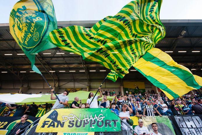 Supporters met vlaggen op de tribune van het ADO-stadion.
