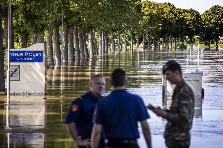 Brandweerlieden en een militair kijken naar het hoge water van de Maas.