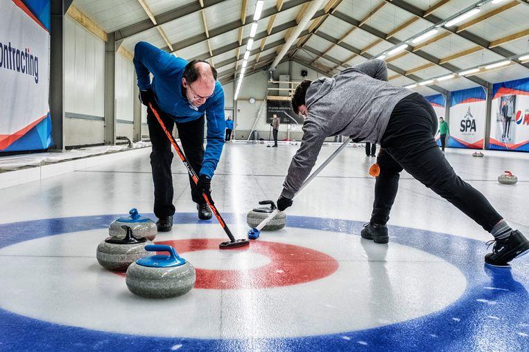 Hard werken in de nieuwe curlinghal in Zemst. 'Natuurlijk zitten wij ook in de fitness. Om goed te kunnen vegen, moet je nu eenmaal getrainde borstspieren hebben.' Beeld Tim Dirven