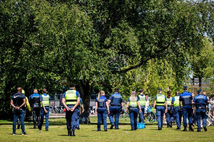 Handhavers en politie ontruimen Park Somerlust vanwege de te grote drukte.