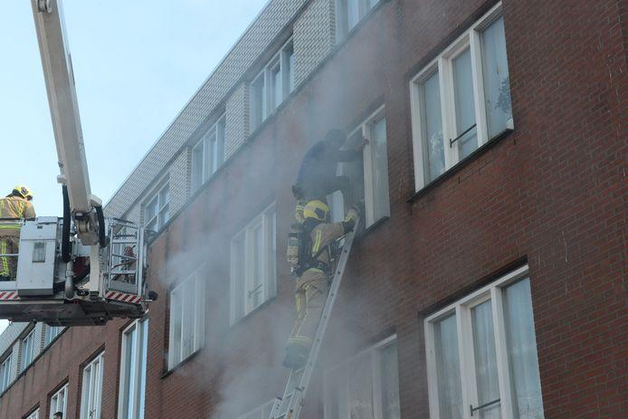 Uit de brandende woning worden mensen gered.
