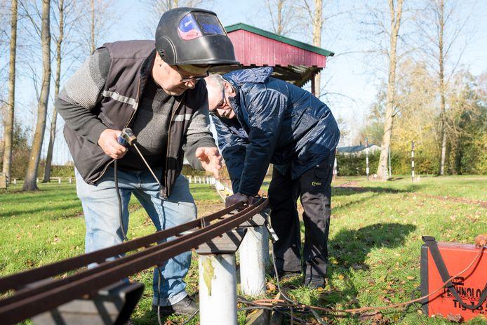 Sig Wollburg (met laskap) en Bas Barendrecht zijn bezig met het herstellen van de hoge baan