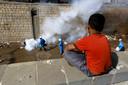 Een Yemenitisch jongetje ziet hoe gezondheidswerkers ontsmettingsmiddel in zijn buurt spuiten tijdens deze nieuwe golf van cholera.