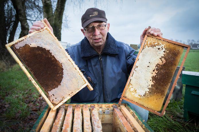 Imker Johan Wichink uit Heeten toont de halfvolle raten die zijn achtergebleven in de vijf verlaten bijenkasten.