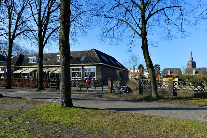 Het schoolgebouw van de Bienekebolders aan de Bosstraat, waar de kerktoren van Moergestel bovenuit steekt.