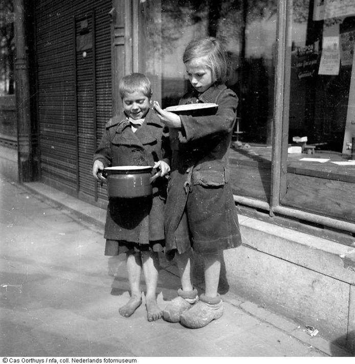 Twee kinderen dragen in de hongerwinter een pan voor zich uit, Amsterdam (1944-1945) F