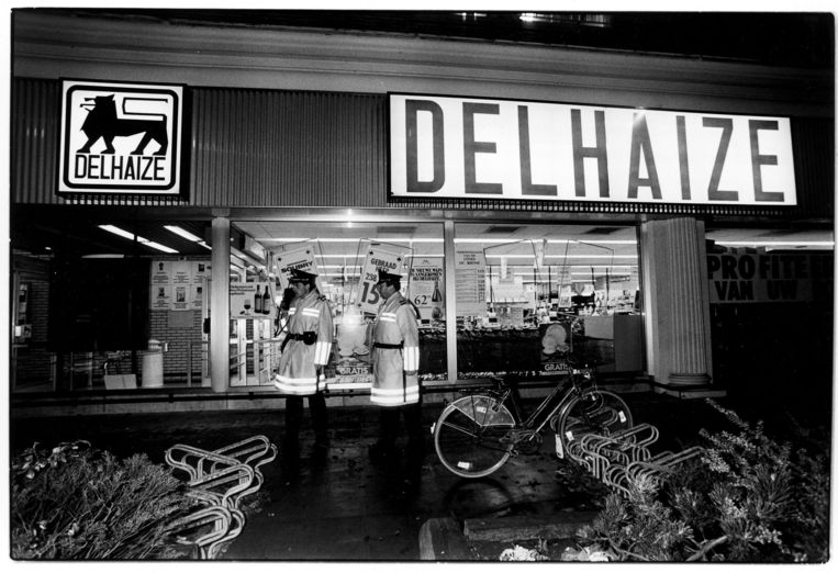 ► Politieagenten voor de Delhaize in Aalst na de dodelijke raid van de Bende van Nijvel in 1985. Beeld Photo News