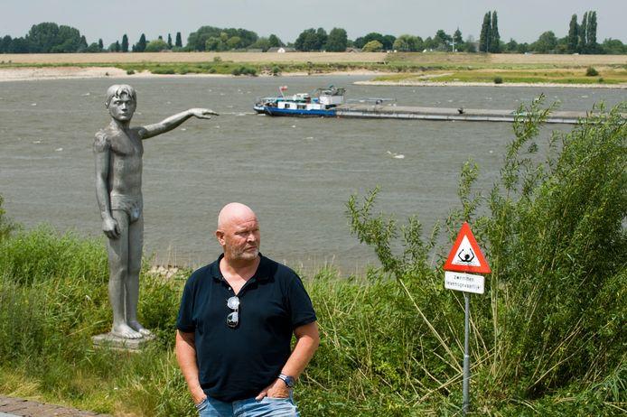 Harry de Bont bij een van de waarschuwingsborden langs de Waal.