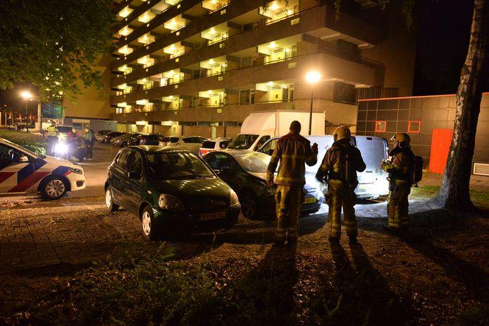 De brandweer bekijkt met een zaklamp de schade aan de auto die in de brand stond.