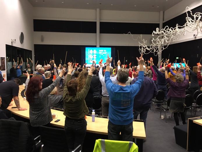 Deelnemers afvalproef Oss dansen op de klanken van gedrum op kliko's.