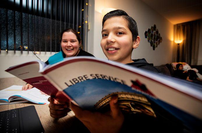 Kim Hofstede en haar zoon Jamal (12). Jamal zit aan de keukentafel en moeder helpt met overhoren