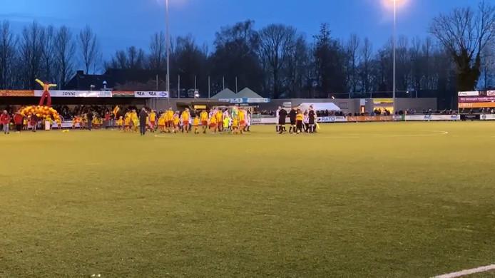 De spelers van Go Ahead Kampen en KHC komen het veld op, terwijl de Champions League-hymne klinkt.