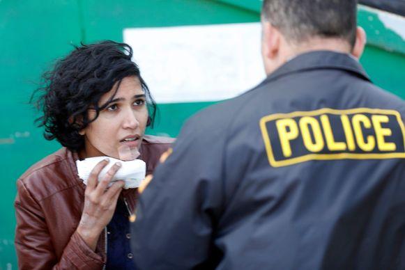 Een gewonde vrouw praat met een politieagent.