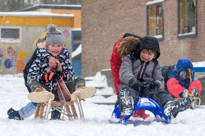 Kinderen spelen in de sneeuw op de eerste schooldag na de lockdown bij basisschool de Dorendal in Doorwerth.