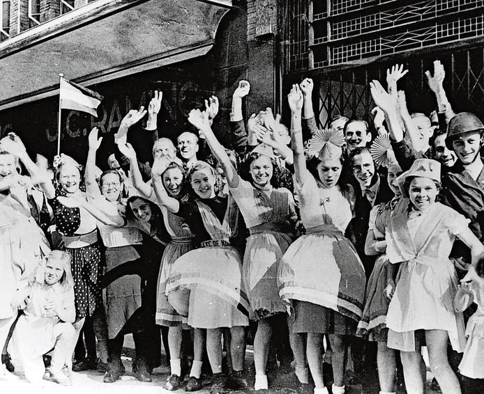 Toeschouwers juichen en zwaaien naar de geallieerden tijdens de intocht van de bevrijding van Nederland.