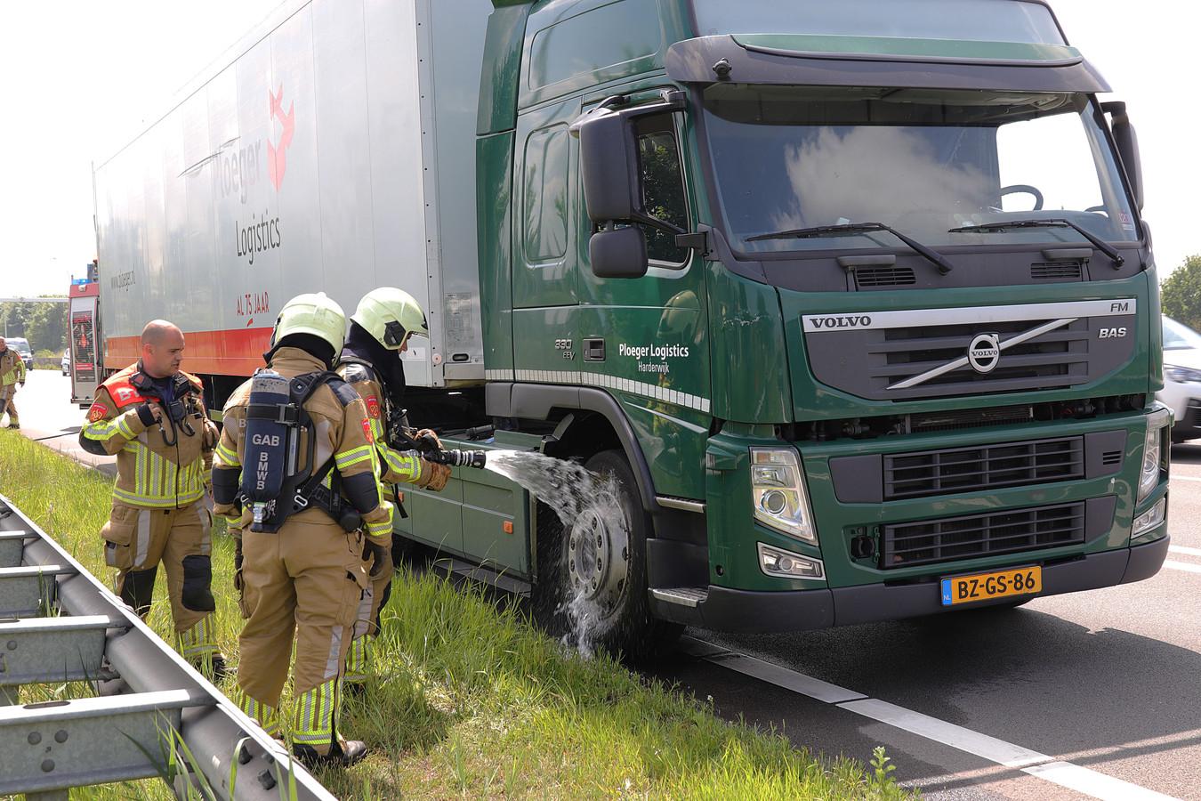 De brandweer koelt de remmen van de vrachtwagen