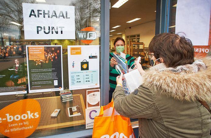 Medewerkster Maartje Kroeze van de bibliotheek in Heeswijk-Dinther geeft gereserveerde boeken mee door het raam van de bieb.