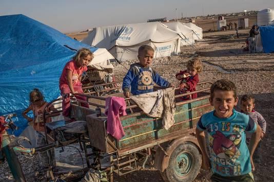 Kinderen in een Syrisch kamp spelen op een aanhangwagen