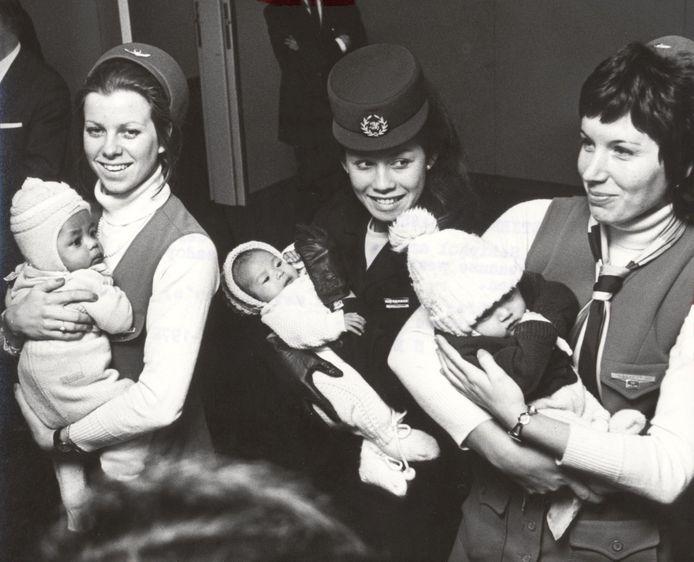 Drie stewardessen met Koreaanse weeskinderen op Schiphol in februari 1972.