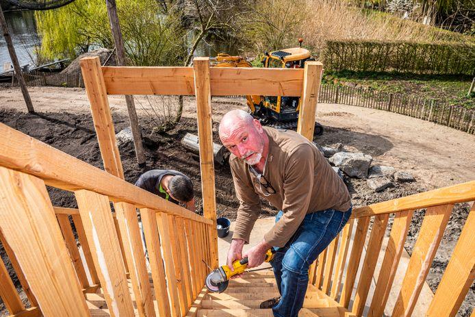 Dierentuinontwerper Jan Kempe maakt nieuw hout 'oud en verweerd' met een slijptol.