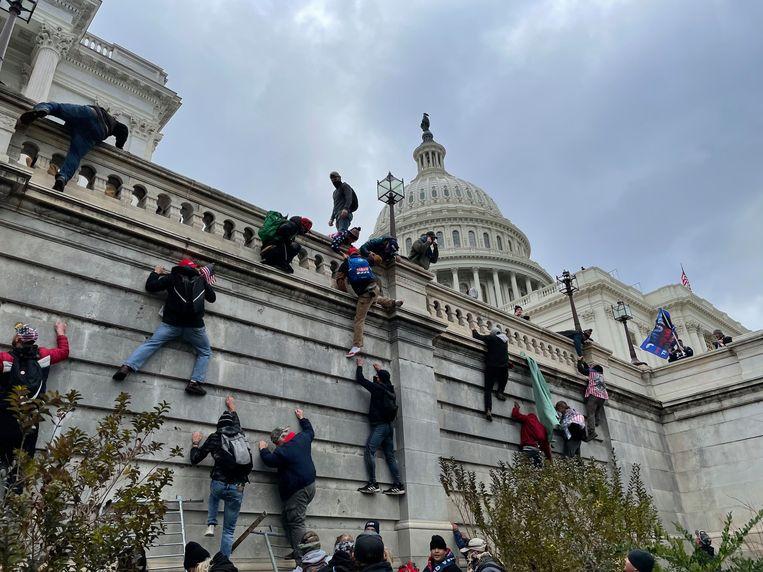 Relschoppers beklimmen de muren van het Capitool. Beeld Photo News