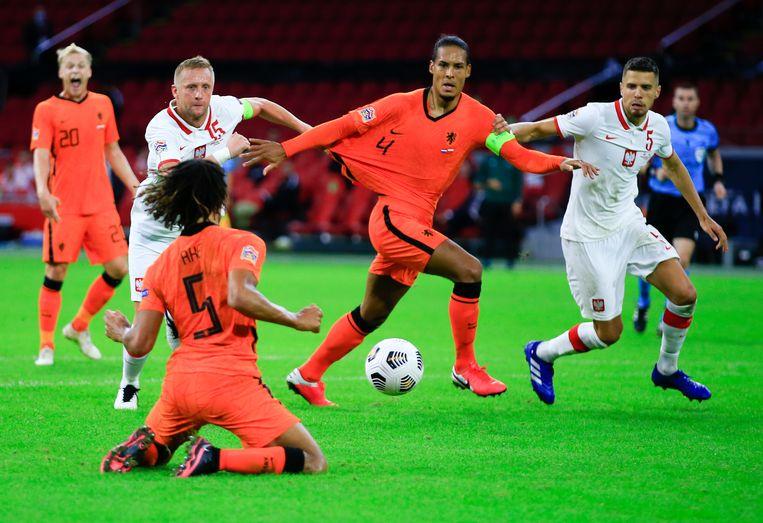 Aanvoerder Virgil van Dijk tussen twee Poolse spelers. Beeld AP