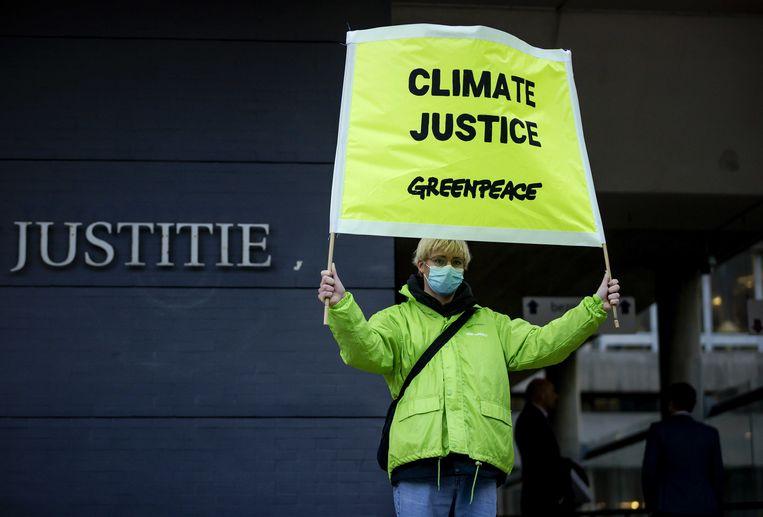 Een medewerker van Greenpeace staat met een spandoek bij de rechtbank tijdens een kort geding tegen de staat over duurzaamheidsvoorwaarden voor de  miljardensteun die KLM vorig jaar van het kabinet heeft gekregen. Beeld ANP