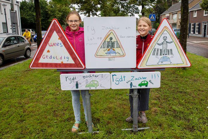 De onthulling van de verkeersborden die ontworpen zijn door een aantal leden van de jeugdgemeenteraad, met Joline Bruggeman (l) en Juka de Bruin.