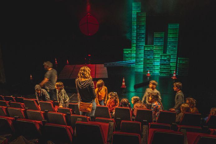 De kindjes kijken vol spanning uit naar het begin van de voorstelling in de kleine zaal.