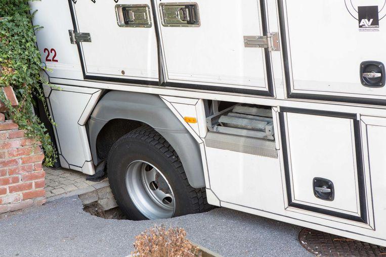 Het rechterachterwiel van de vrachtwagen zit vast in het zinkgat.