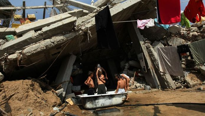 Palestijnse kinderen nemen een bad naast hun vernielde huis in Jabalia, in de Gazastrook.