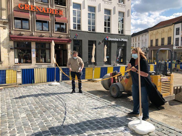 Michel en Claudine van de Grenadier meten op waar ze een terras kunnen plaatsen tussen de werken op de Grote Markt.