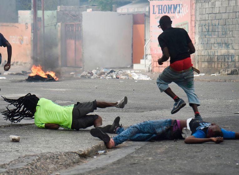 Een man valt terwijl hij het lichaam van een dode kameraad mee wil slepen in Port-au-Prince. Beeld AFP