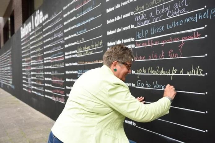 De 'Before I die'-wand waar mensen wensen op konden schrijven.