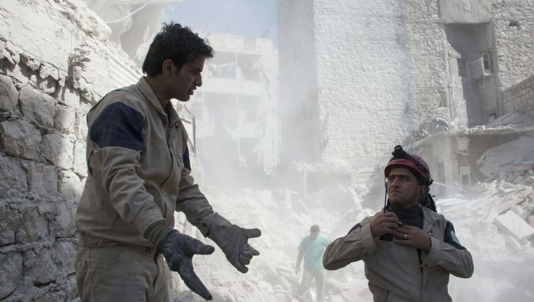 Ismail Alabdullah (links) in actie als reddingswerker van de White Helmets. 'Soms treffen we kinderen zonder hoofd aan.' Beeld White Helmets
