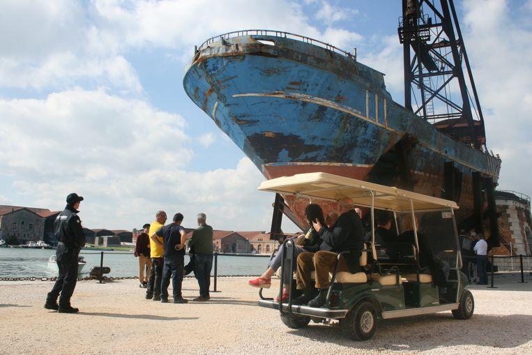 Bezoekers passeren 'Barca Nostra', het kunstwerk van Christoph Büchel op de 58ste Biënnale van Venetië. Deze vissersboot verging tussen Libië en Lampedusa in april 2015: honderden migranten zaten vast in het ruim en verdronken. Beeld Anna van Leeuwen