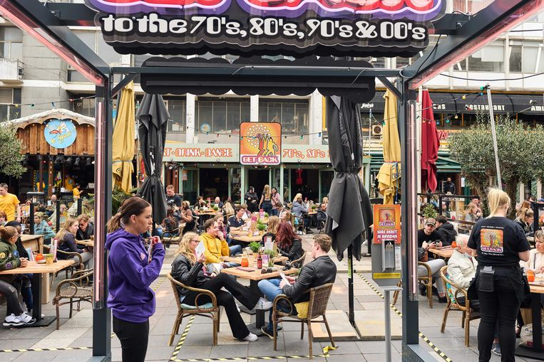 Mensen op een vol terras op het Stadhuisplein in Rotterdam. Uit onderzoek blijkt dat één van de vijf Nederlanders van plan is zelfs meer geld uit te gaan geven aan uit eten gaan of vakanties dan voor de lockdowns.  Beeld ANP