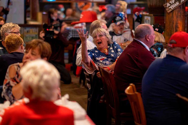 Het publiek reageert op de verkiezingsuitzending van Fox News op een kijkfeest georganiseerd door de groep 'Villagers for Trump' in The Villages in de staat Florida op 3 november 2020. Beeld AFP