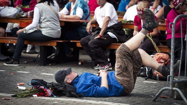 Een man ligt op de grond met zijn benen omhoog uitrusten na de finish van de Nijmeegse Vierdaagse, vandaag. Beeld anp