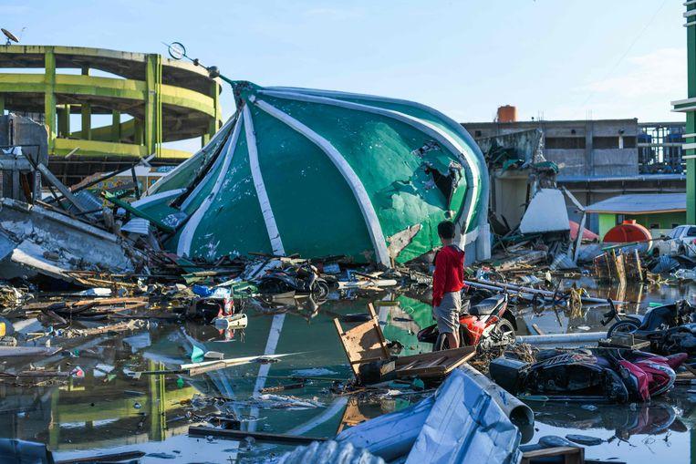 Een slachtoffer dwaalt door de rest van een zwaar getroffen wijk in de stad Palu. Beeld AFP