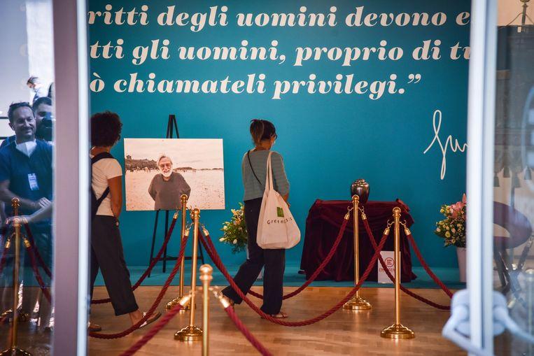 'Mensenrechten moeten de rechten van iedereen zijn, echt van iedereen, anders moet je ze privileges noemen', staat op de wand bij de condoleance voor Gino Strada in Milaan. Beeld EPA