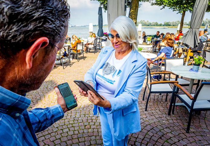 Yvonne Kilsdonk van café-restaurant Jongepier in Dordrecht checkt de QR-code in de CoronaCheck-app van een klant die naar binnen wil.