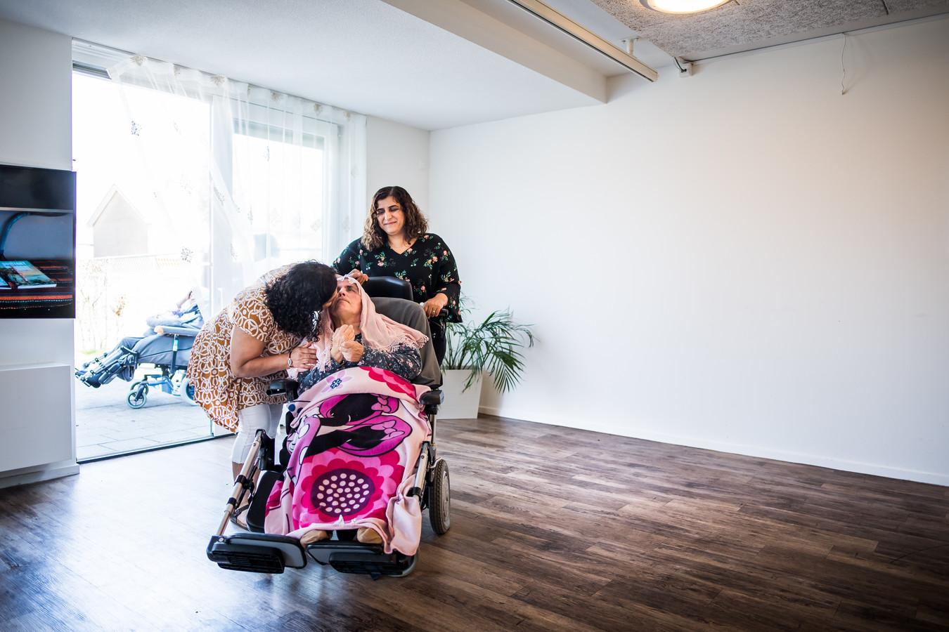 Solmaz Yildiz knuffelt haar moeder, terwijl Zahide Guneri de rolstoel voortduwt.