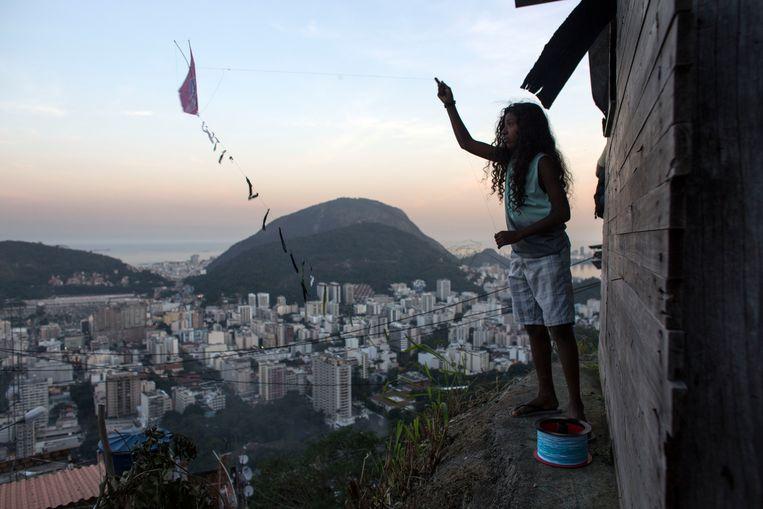 Een tienjarig meisje uit de sloppenwijken van Rio de Janeiro speelt met een vlieger in het aanschijn van een rijker stadsdeel. Beeld BELGAIMAGE
