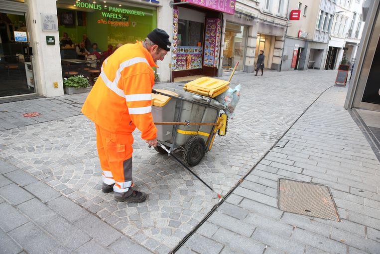 Straatveger Marcel Rimez aan de slag met grijper in de Basiliekstraat op zijn dagelijkse ronde.