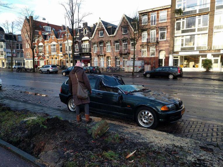 Deze auto op de Middenweg werd geplet door een omgevallen boom. Beeld Rob van Leeuwen