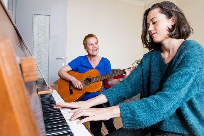 Samen vormen muziektherapeutes Manon Misonne (vooraan, aan de piano) en Femke Bauwens (op gitaar) Kleinnood, een vzw die liedjes op maat componeert voor mensen die een zwaar verlies of verdriet moeten torsen.