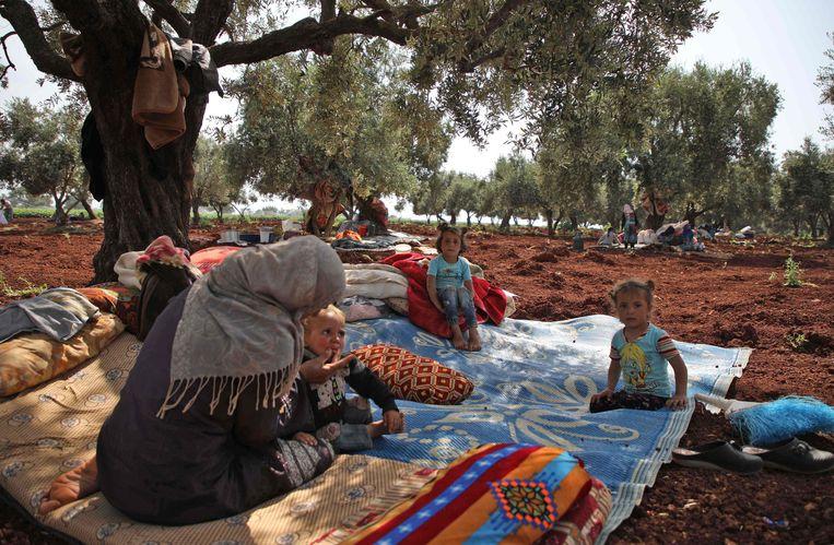 Gevluchte Syriërs onder een boom, vlak bij een vluchtelingenkamp in het dorp Atme, Idlib, op 1 mei.  Beeld AFP