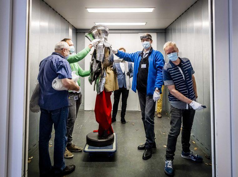 Een mogelijke extra maatregel is een tijdelijke sluiting van musea. Medewerkers van de Hermitage verplaatsen een Duits toernooiharnas uit circa uit 1500 voor een tentoonstelling.  Beeld ANP